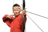 Young archer concentrating and aiming, frontal view poster