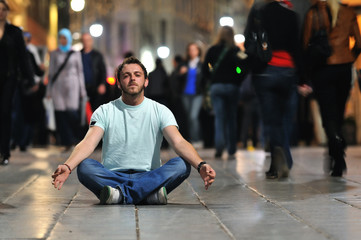 young man meditating yoga in lotus position at street