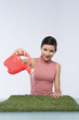 Beautiful girl watering artificial grass
