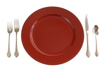 Table setting with red plate and silverware on white
