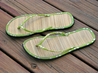 pair of summer sandals on wood deck