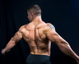 A perfect muscular man posing artistic, back double biceps poster