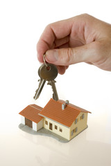 businessman hand with keys and a little house