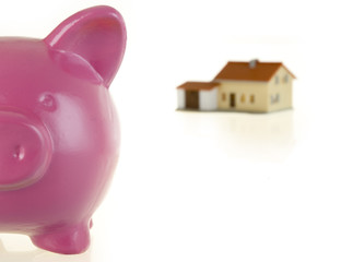 piggy bank and little house isolated on white
