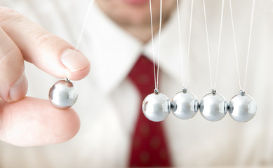 Businessman hand holding a pendulum ball