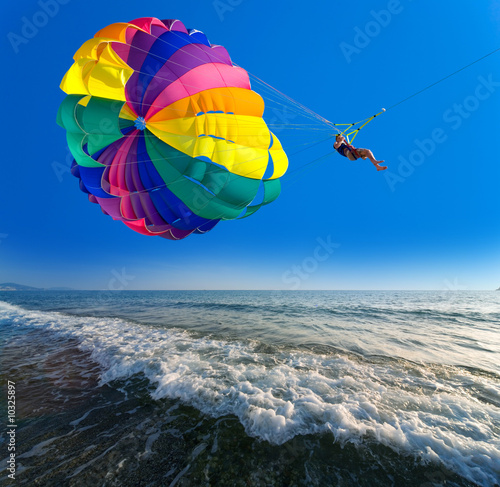 Man is parasailing in the blue sky