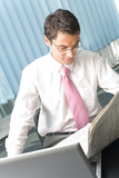 Young businessman reading fresh newspaper at workplace poster