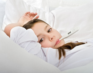 young girl lying in bed with a thermometer