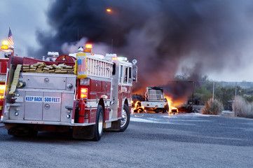 Firemen fight a fire that has involved  industrial trucks.