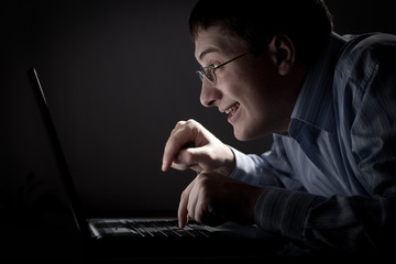 crazy young adult man with working at night with laptop