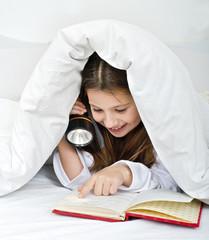 girl reading under blanket with flashlight