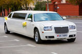 White wedding limousine on the road. Ornated with flowers. - Fine Art prints