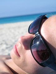 female with shades on the beach