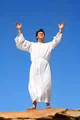 A man raises his arms  heavenward in an act of worship