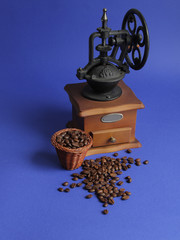 Retro style coffee mill with coffee beans skattered on blue