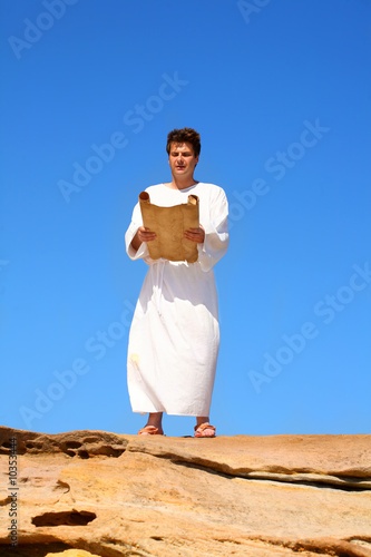 A man in a white robe reads from a scroll desert landscape
