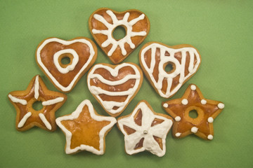 Decorated star and heart cookies on green paper