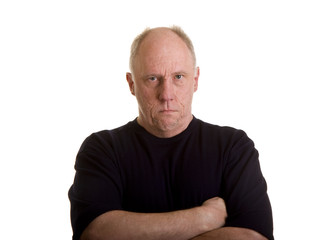 An older bald man in a black shirt looking angry or mad