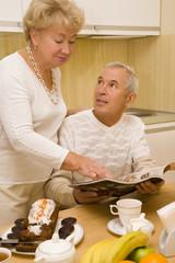 Elderly couple look a magazine during breakfast