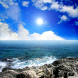Sea landscape with cloudy sky and sun