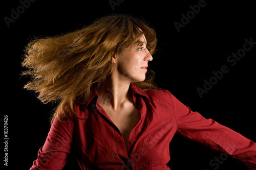Beautiful woman flipping hair, isolated on black background