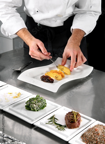 Chef preparing food on professional kitchen in restaurant