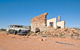 old car and ruins of a building in the desert