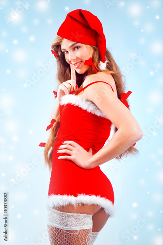 Sexy mrs. Santa smiling and posing on blue backround