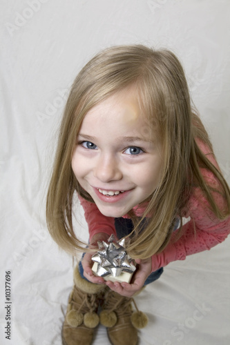 Young girl bent forward as if skeaking with a gift in her hand.