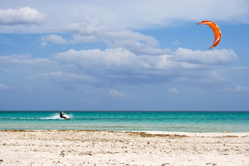 A kitesurfer gliding at high speed around the beach Cinta