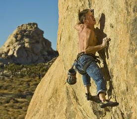Climber ascending a steep rock face.