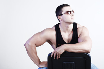 portrait of strong athlete in black undershirt and sun glasses