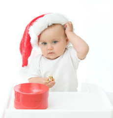 little, cute baby boy wearing Christmas hat, on white