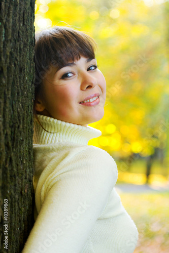 girl smiles around tree