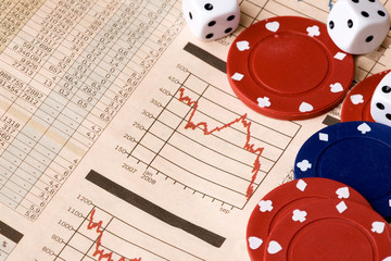 dice and casino chips on a stock market chart