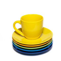 Yellow teacup and stack of saucers isolated on white.
