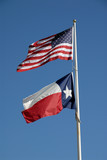 Texas and United States flags against blue sky poster