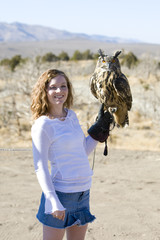 pretty girl holding an owl in the desert