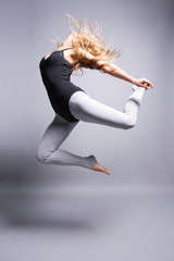 beautiful ballet dancer jumping on grey background