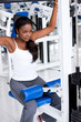 black woman at the gym doing back exercises on a machine