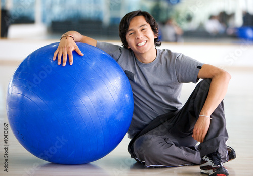 gym man doing pilates exercises on a blue ball