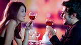 Young couple celebrating with red wine at restaurant - Fine Art prints
