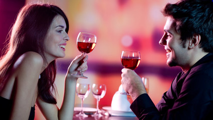 Young couple celebrating with red wine at restaurant