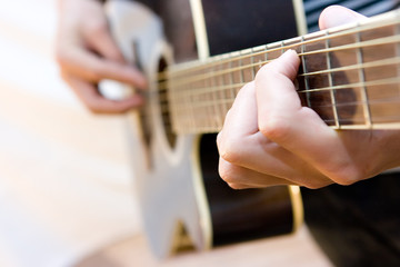 Young artist playing guitar on white background