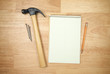 Pad of Paper, Pencil, Hammer and Nails on a Wood Background.