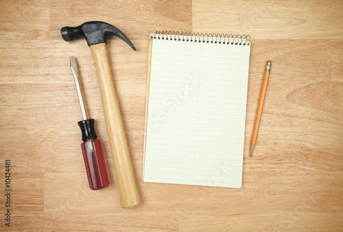 Notepad, Pencil, Hammer, Screwdriver on a Wood Background.