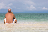 young man relaxing, sitting on sandbank in clear blue water poster