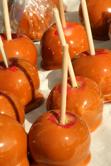 A Bunch of carmel apples with sticks
