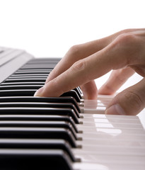A musicians hand on a keyboard isolated on white