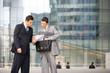 hommes d'affaires négotiant un contrat devant immeuble